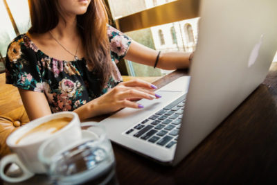 Brunetka pożyczająca na dowód przez komputer - z kawą
