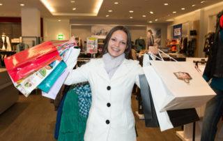 Kobieta na zakupach z wieloma torbami - karty lojalnościowe