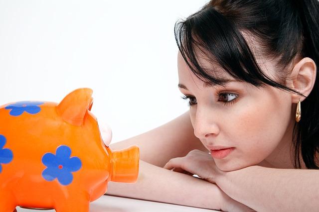 Kobieta wpatrzona w pomarańczową skarbonkę świnkę