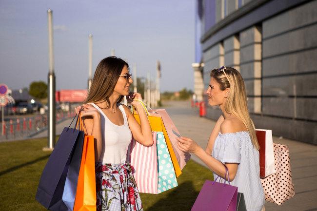 Rozmawiające kobiety - obładowane torbami z zakupami - wydatki