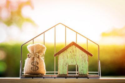 Worek pieniędzy z podatków i domek za kratami